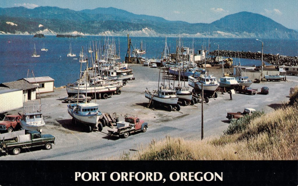 View showing the dock and fishing fleet. Note the boats are lifted out of the water and placed on the dock. Humbug Mountain is in the distance. (Text on postcard) c1980.  Behind the hoist is the FV Amak anchored stern first.